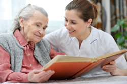 caregiver and senior reading a book